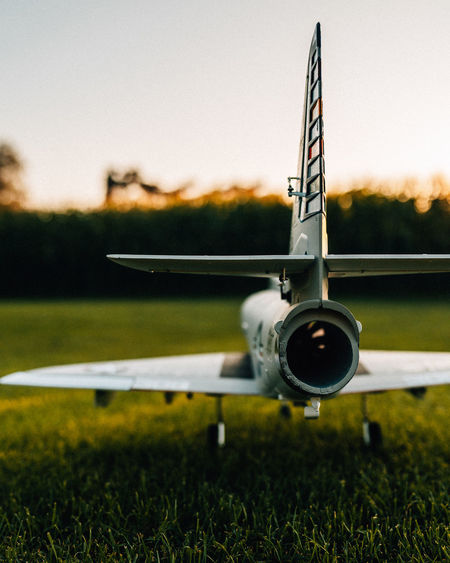 Close-up of model airplane on runway against sky