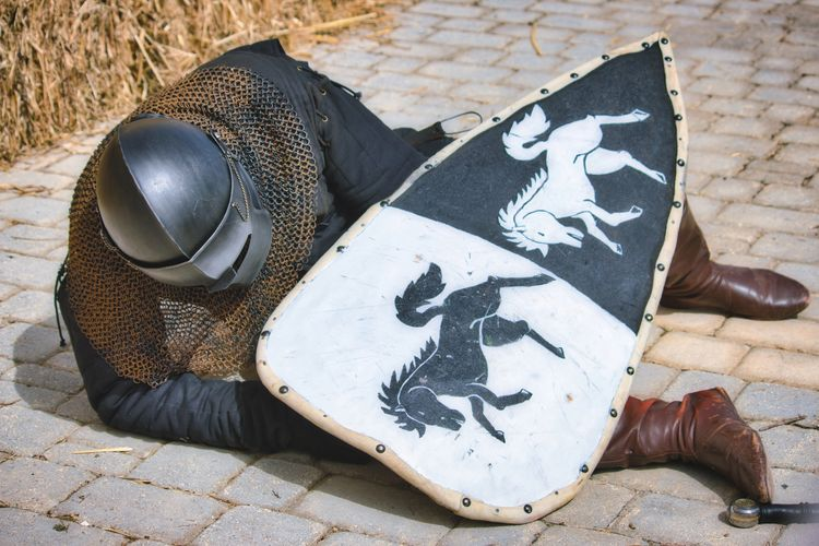 High angle view of man in armor suit sitting on footpath