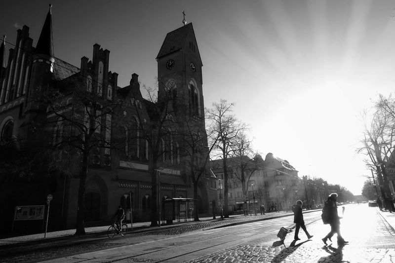 crossing the Street High Noon Backlight Sun Sunlight Church Silhouette City Clock Built Structure Architecture Tree People Day Schwarzweiß Monochrome Blackandwhite Sunlight And Shadow Sunny Day Winter Cobblestone Tram Line Streetphotography Beautiful Day The City Light