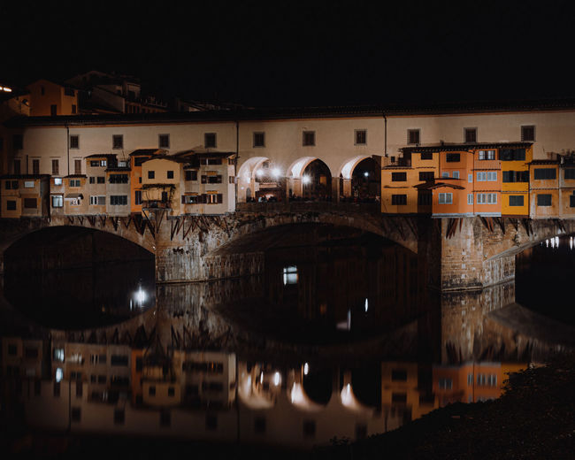 Arch bridge over river in town against sky at night