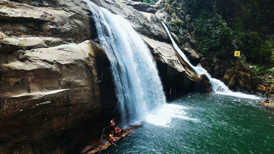 People by waterfall on wooden raft
