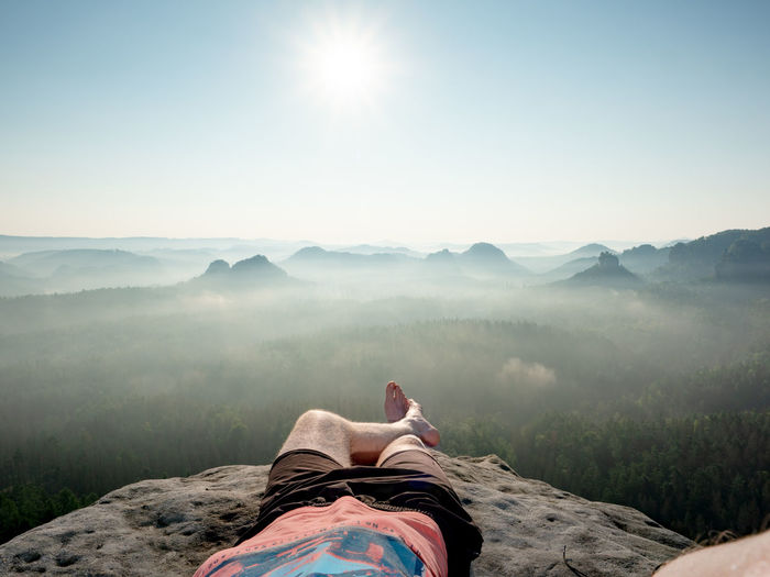 Hiker with bare feet lie on  edge of rock and relax. view over resting male body into morning land