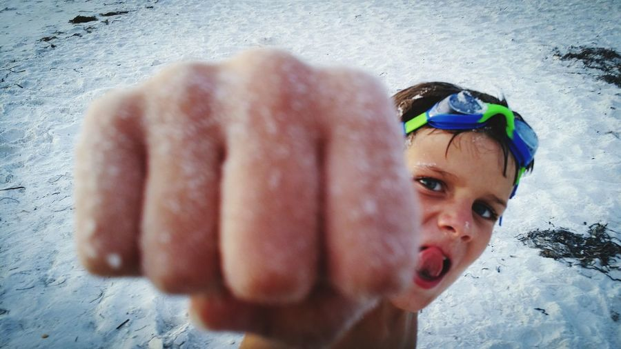 Close-up high angle portrait of cute boy punching at beach