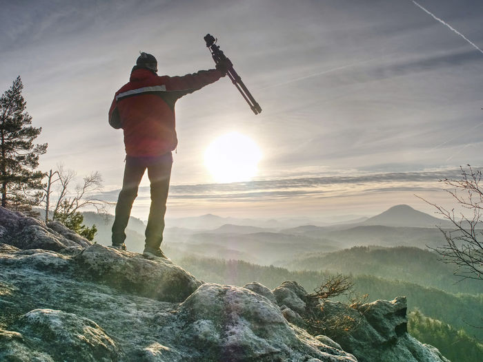 Tourist hold travel tripod. photographer climbed on peak for photographing the sunrise from mountain