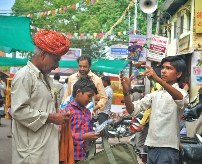 Father and son buying helicopter toy from vendor at street
