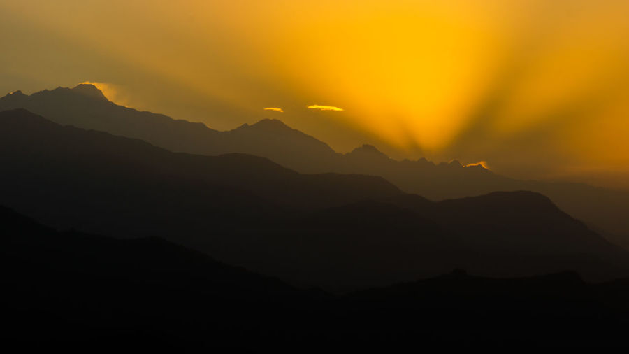 Silhouette of mountain against sky at sunset