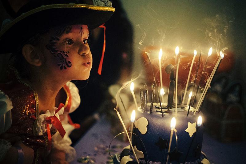 Illuminated candles in dark room