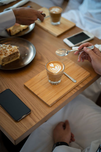 Coffee on Wooden Table in Cafe Real People Table Food And Drink Human Hand Hand High Angle View Human Body Part Lifestyles Indoors  Men Drink Holding Adult Refreshment One Person Women Leisure Activity Cup Mug Ijas Muhammed Photography Coffee Restaurant