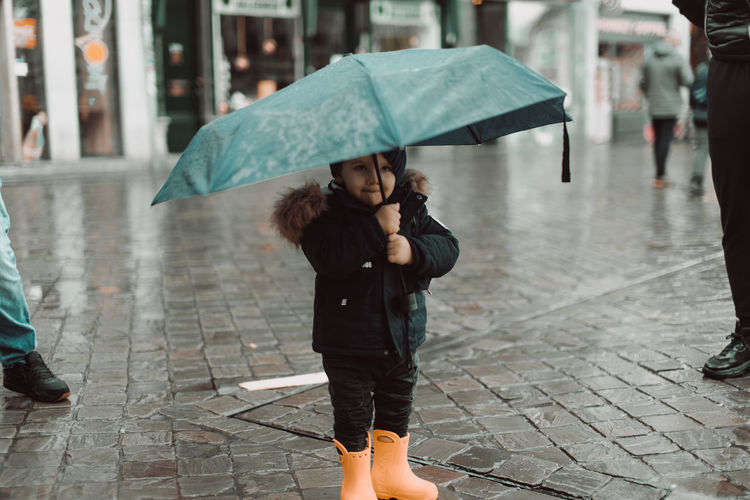 Cuty boy with an umbrella under the rain