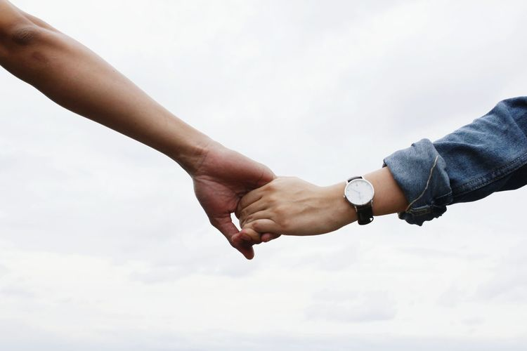Close-up of couple hands against sky