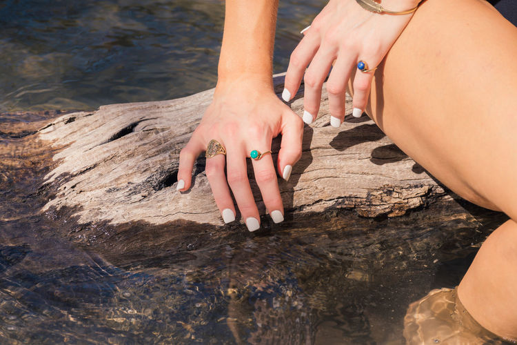 Midsection of woman showing white nail polish at lake on sunny day
