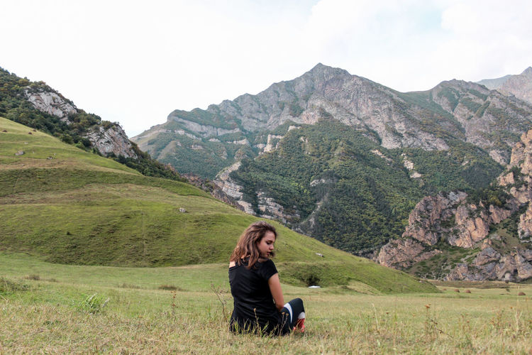 Rear view of young woman sitting on field against mountain range