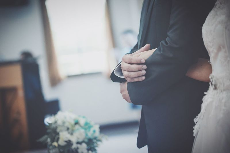 Midsection of couple holding hands at wedding ceremony
