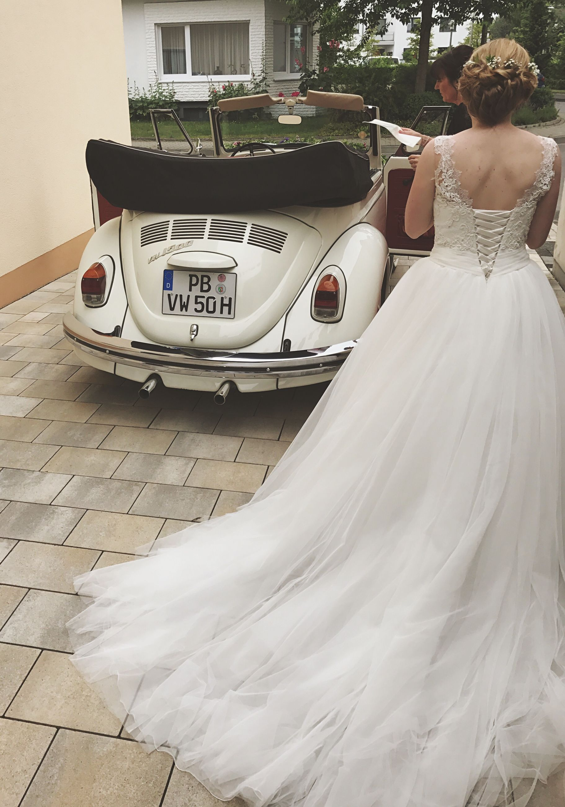 wedding, bride, mode of transport, car, real people, land vehicle, transportation, wedding dress, day, life events, one person, women, celebration, outdoors, built structure, standing, building exterior