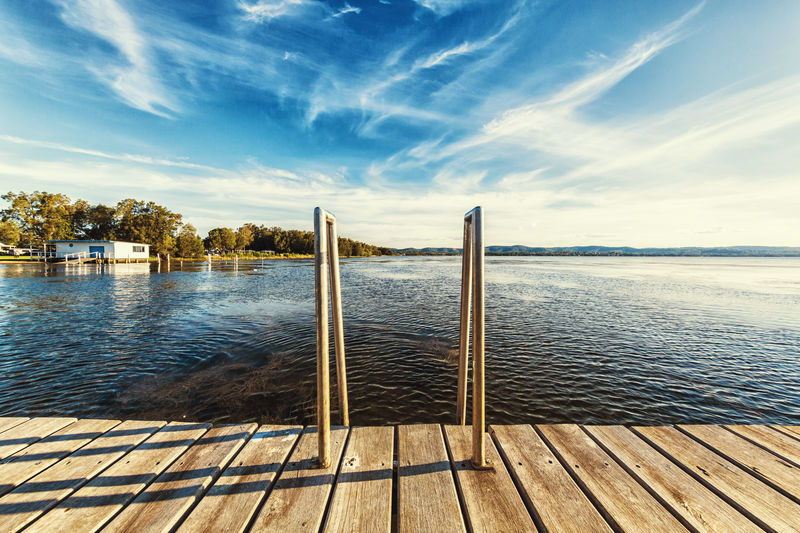 A jetty and a ladder into the calm waters of a lake on a clear sunny day with a blue sky. Calm Dive In Holiday Ladder Pier Serenity Sunny Swimming Travel Blue Sky Boardwalk Cloud - Sky Horizon Jetty Lake Nature No People Peaceful Platform Sea Sky Swim Tranquil Scene Travel Destinations Water
