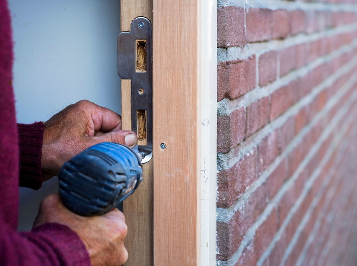 Close-up of man working on door