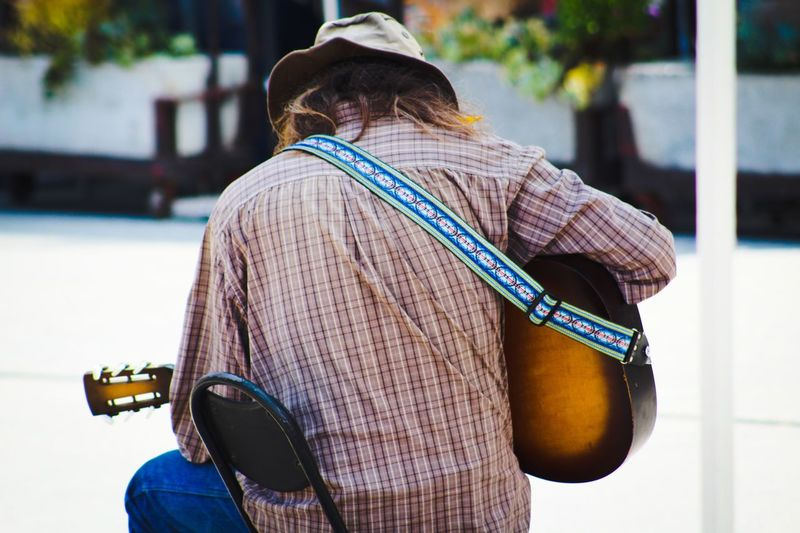 Rear view of man playing guitar on street