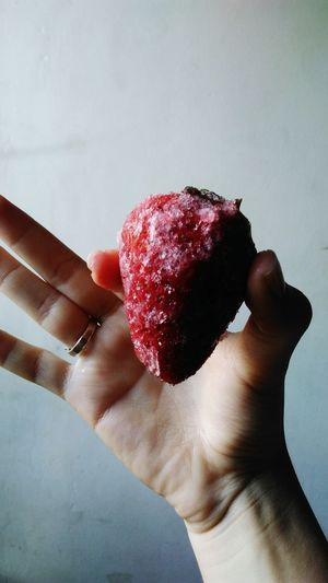 Cropped image of person holding frozen strawberry against wall