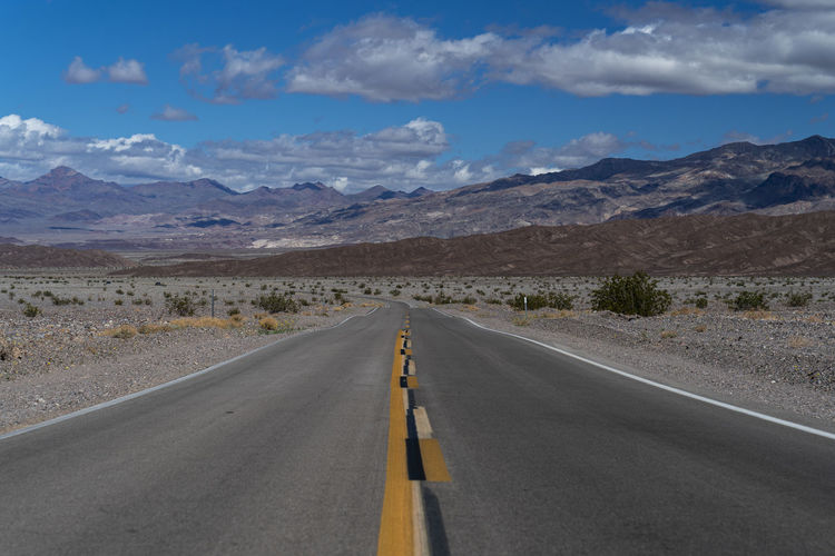 Empty road along landscape and mountains against sky