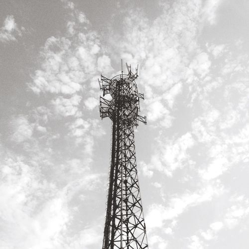 Low angle view of cellular tower against cloudy sky