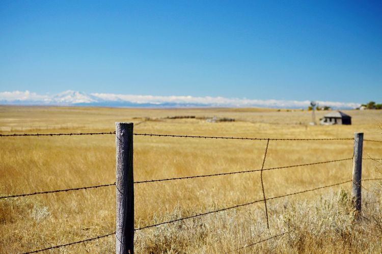 Distant clouds Mountains In Background Corral Sunshine Outdoors In The Distance. Barbed Wire Fence Grass Sky West Of Lusk Wyoming Wooden Post Rural Scene Pasture Ranch