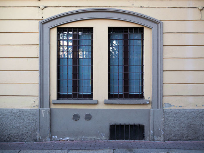 Arch Architectural Detail Architecture Black Windows Blue Building Exterior Built Structure Cement Curb Day Glass Metal Grate No People Old Palace Outdoors Security Bar Self-locking Sidewalk Stone Sidewalk Vent Wall Wall Lines Wall Vent Window Windows