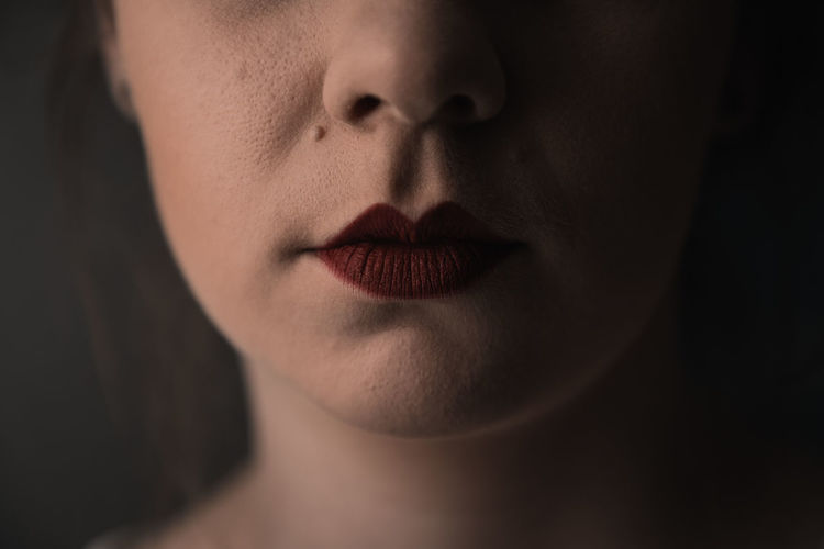 Mysterious portrait of a young female with red lipstick and only half of the face showing
