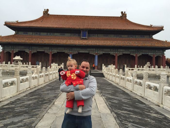 Portrait of man carrying daughter standing at temple against clear sky