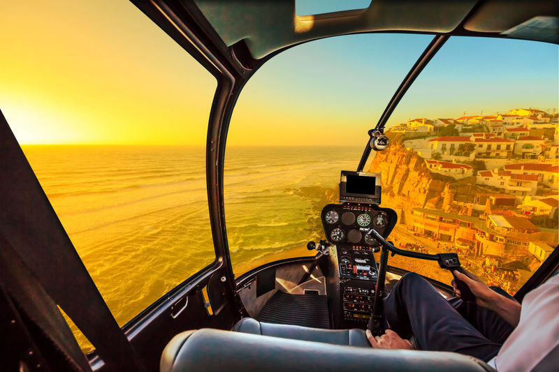 Helicopter cockpit interior flying on Azenhas do Mar beach at sunlight, the Atlantic Ocean in Portugal. Scenic flight above Popular Portuguese seaside skyline near Colares and Sintra municipality. Cockpit View Cockpit Interior Flight Scenic Flight Flying Aerial View Panorama Skyline Beach Sea Seascape Portugal Rock Formation Douro River Portugal Serra Do Pilar Vila Nova De Gaia Oporto City Sunset Window Azenhas Do Mar Ponta Da Piedade Marinha Beach Natural Arch Helicopter Mode Of Transportation Transportation Sky One Person Vehicle Interior Nature Sitting Air Vehicle Horizon Airplane Glass - Material Pilot Day Water Scenics - Nature Outdoors Adult Uniform