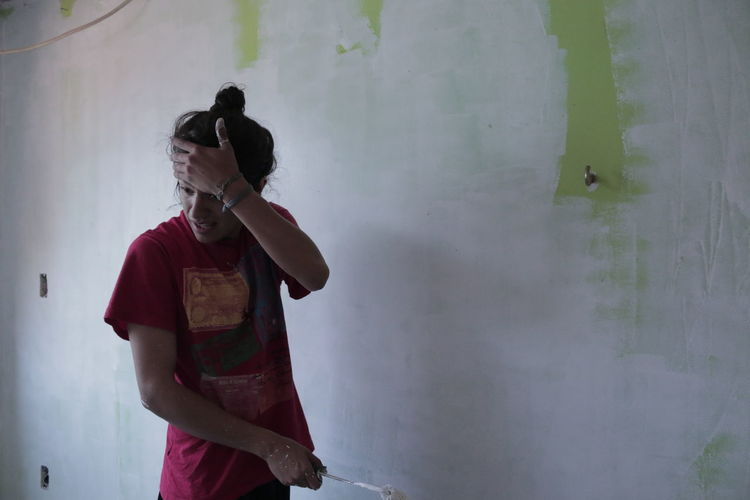 Man with head in hand standing against wall while painting at home