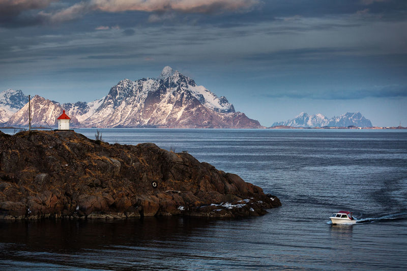 Scenic view of boat in sea by mountains against sky