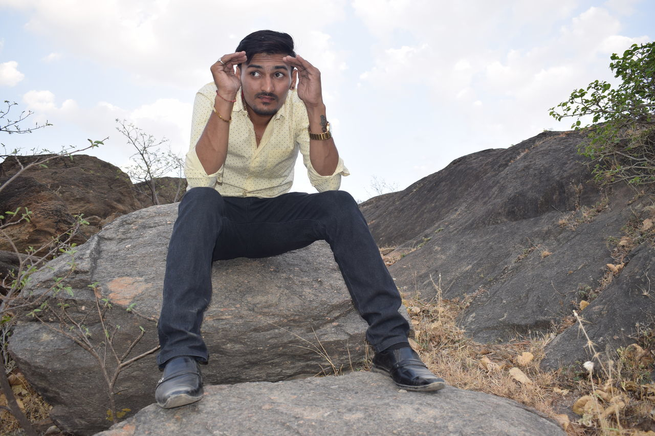 real people, one person, rock - object, young men, casual clothing, full length, young adult, lifestyles, outdoors, mountain, front view, nature, leisure activity, day, sky, looking at camera, sitting, tensed, landscape, beauty in nature