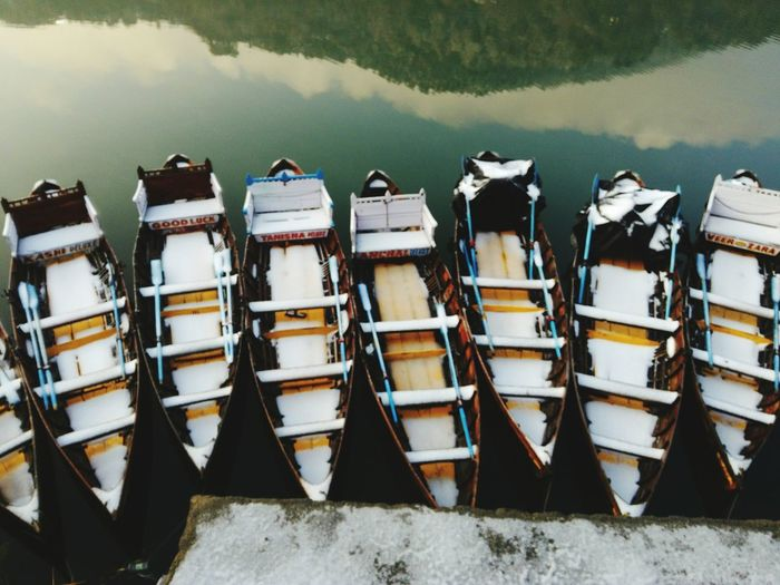 Stack of fishing boats moored in lake