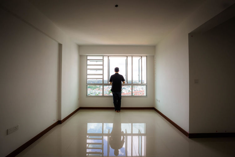 Alone in an empty house Alone Alone In An Empty House Architecture Day Empty Full Length Home Interior Indoors  Lifestyles Looking Out Of The Window Men No Furniture One Person People Real People Standing Unfurnished Home Window A New Perspective On Life A New Perspective On Life