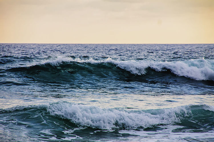 Scenic view of waves splashing in sea