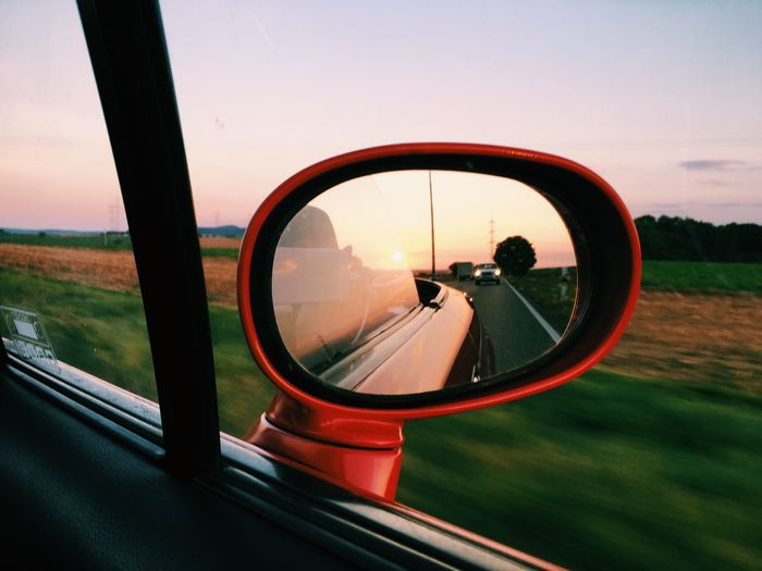 Close-Up Of Side-View Mirror Against Sunset Sky