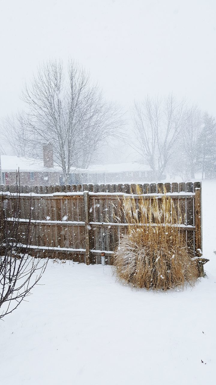 Wooden Fence On Snowy Field During Snowfall