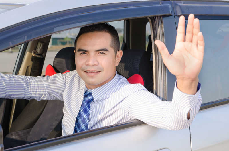 Businessman waving hand while driving car