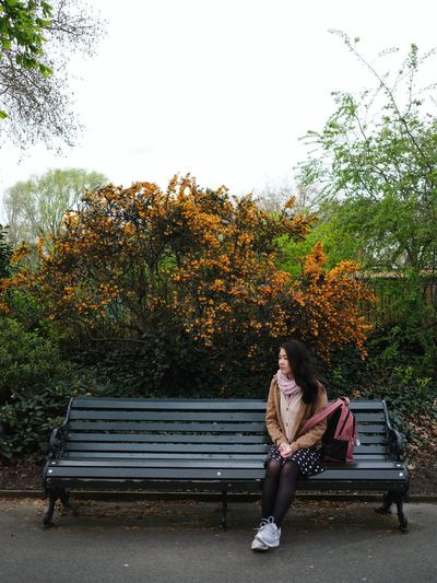 Full length of woman sitting on bench in park