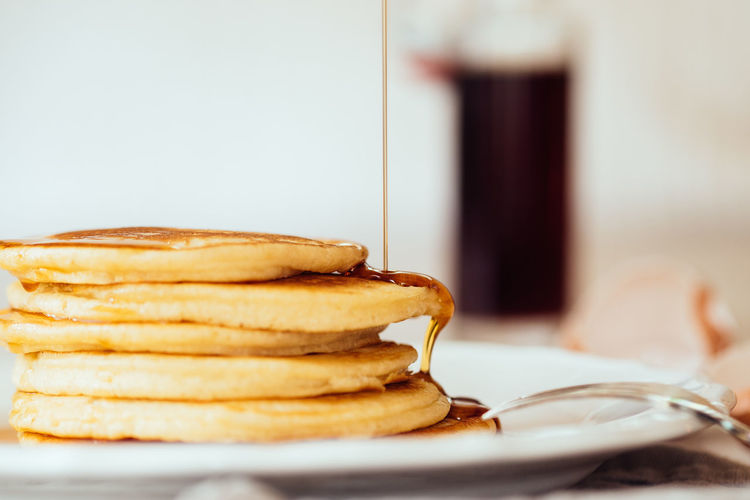 Close-Up Of Maple Syrup Falling On Fresh Pancakes