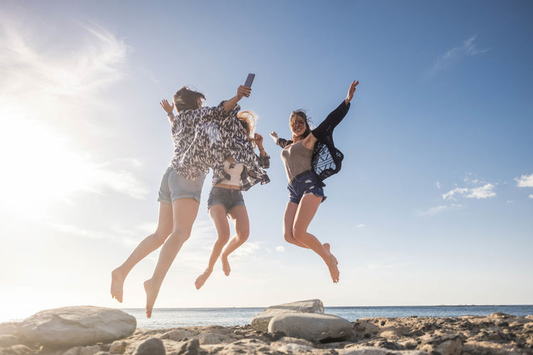 Three young woman jump for happiness. beauty and fun. Beach Blue Carefree Cheerful Day Enjoyment Excitement Full Length Fun Happiness Horizon Over Water Jumping Leisure Activity Low Angle View Mid-air Nature Outdoors Rock - Object Sea Sky Summer Sunlight Togetherness Vacations Vitality