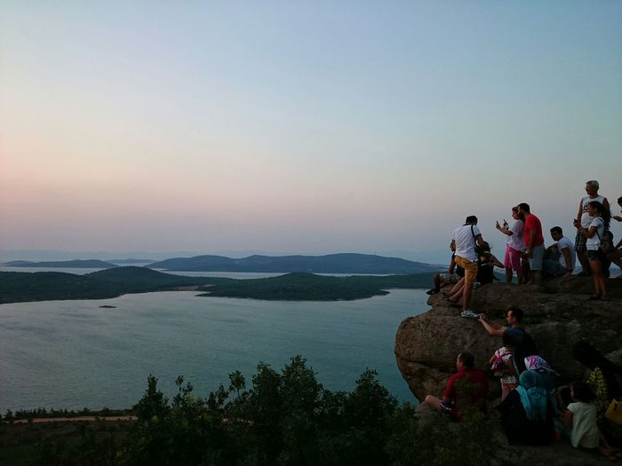 People on rock formation by lake against sky during sunset