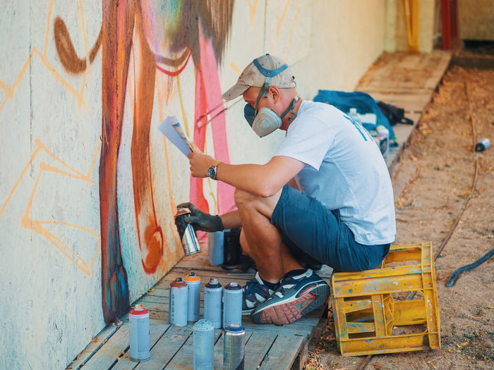 Side view of young man spraying graffiti on wall