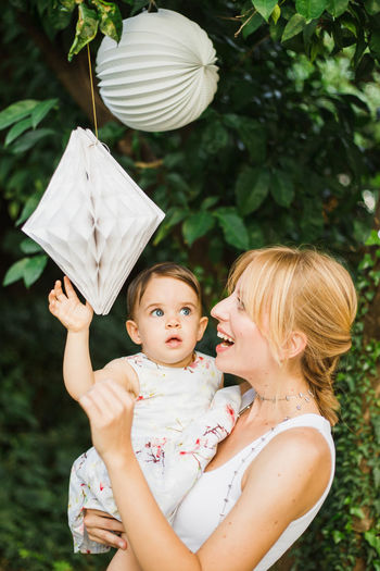 Mother carrying cute daughter touching decorations hanging in yard