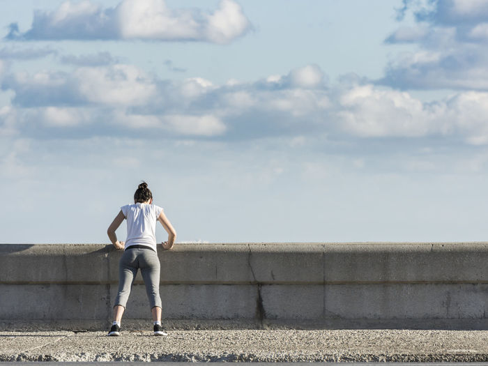 Rear view of woman exercising on seawall against sky