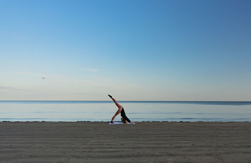 Yong women in pink leggins practicing yoga by the seaside against sky.