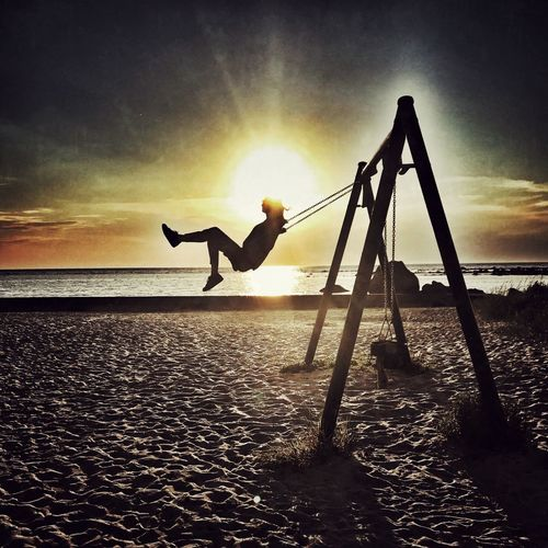 Swinging at sunset near the sea Childhood Memories Childhood Child Swing Sky Water Sunset Sea Silhouette Real People Sunlight One Person Leisure Activity Sun Bright EyeEmNewHere