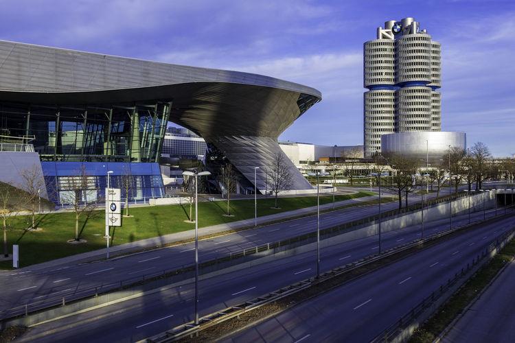 Road by modern buildings against sky in city