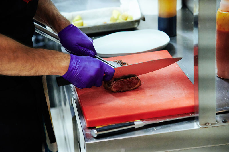 Midsection of man slicing food in restaurant kitchen