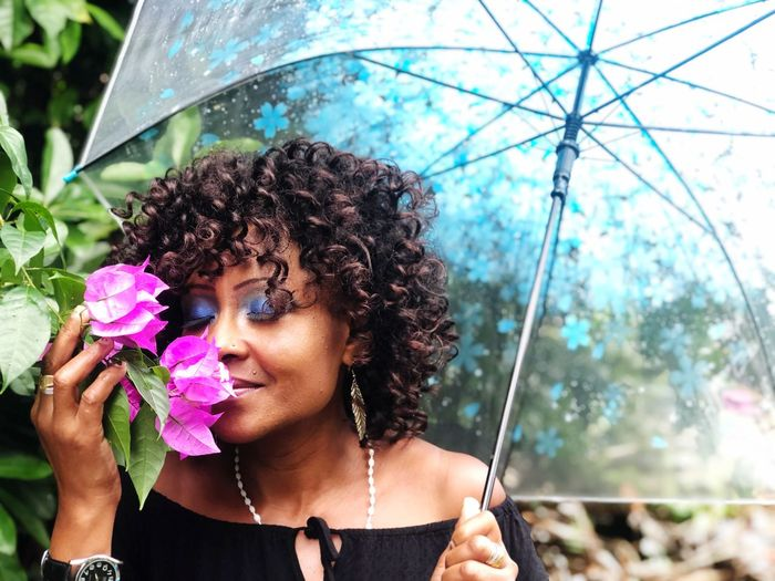 Mature woman with curly hair holding umbrella while smelling flowers